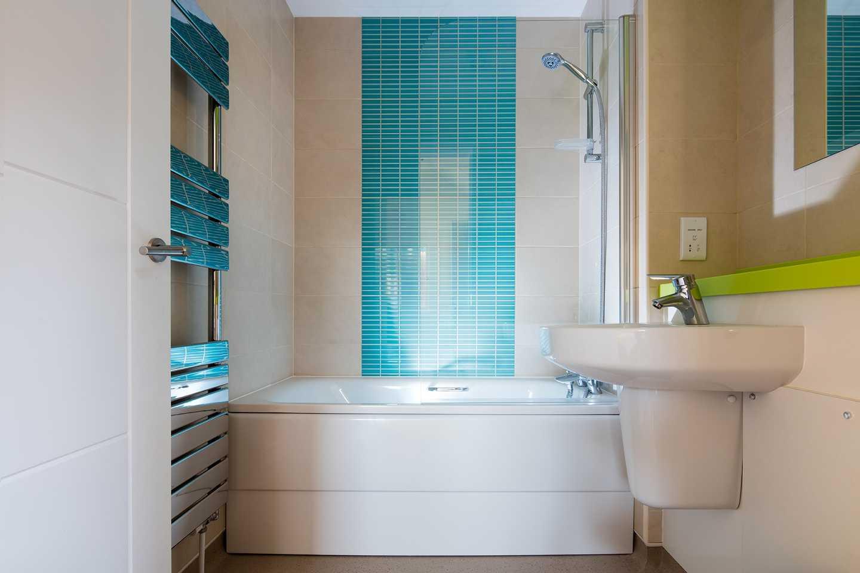 A Deck house bathroom with heated towel rack, bath, shower, sink and mirror
