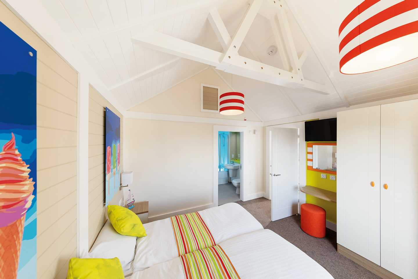 A Deck house twin bedroom with two beds, wardrobe, side table, TV and mirror