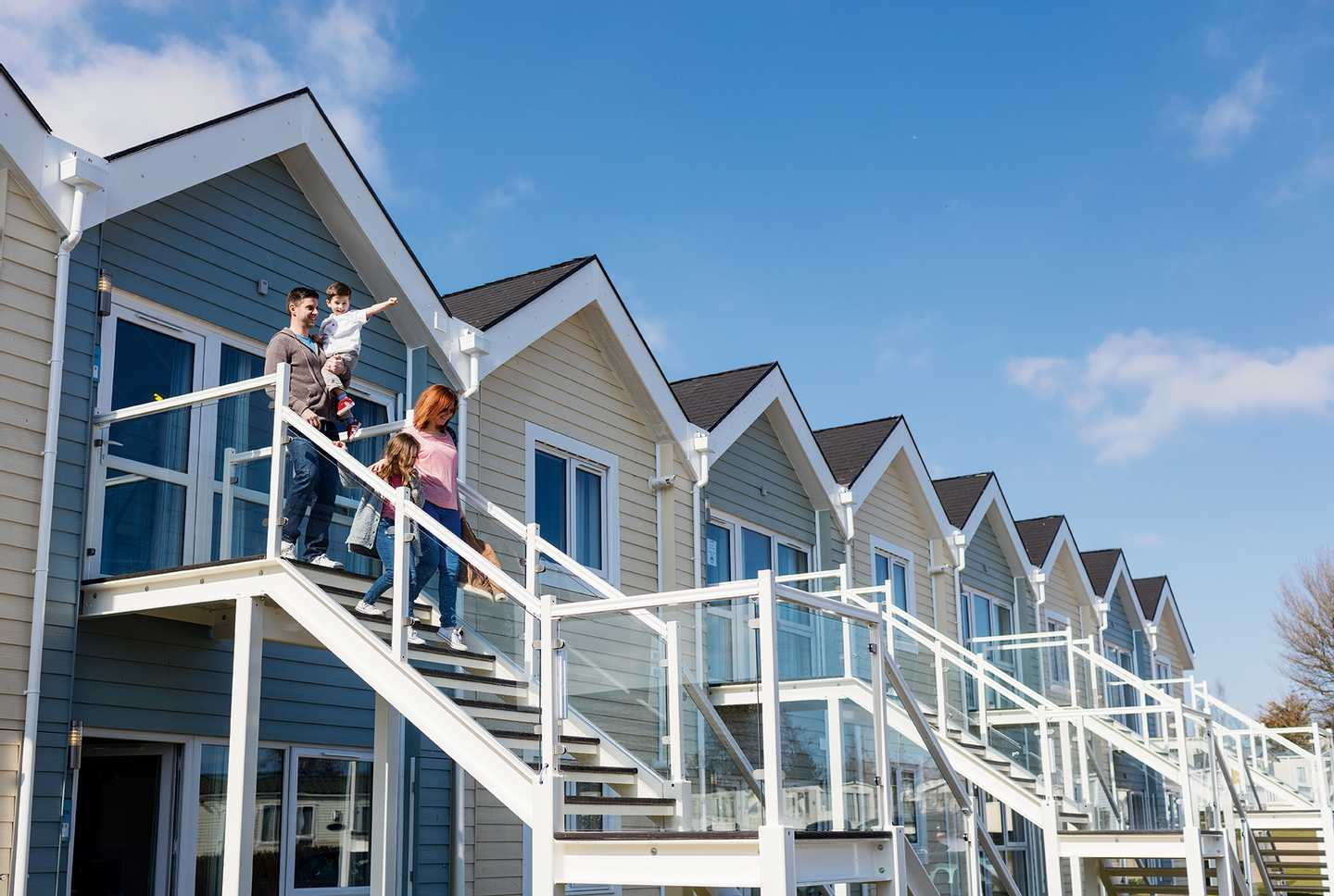 A family walking down the steps of a Deck House on a sunny day