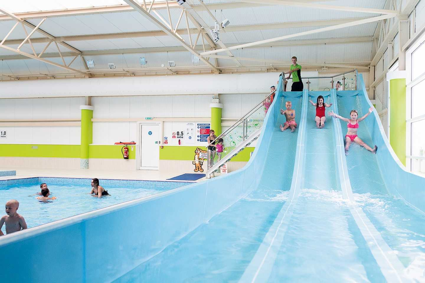 Children whizzing down the slides in our indoor pool