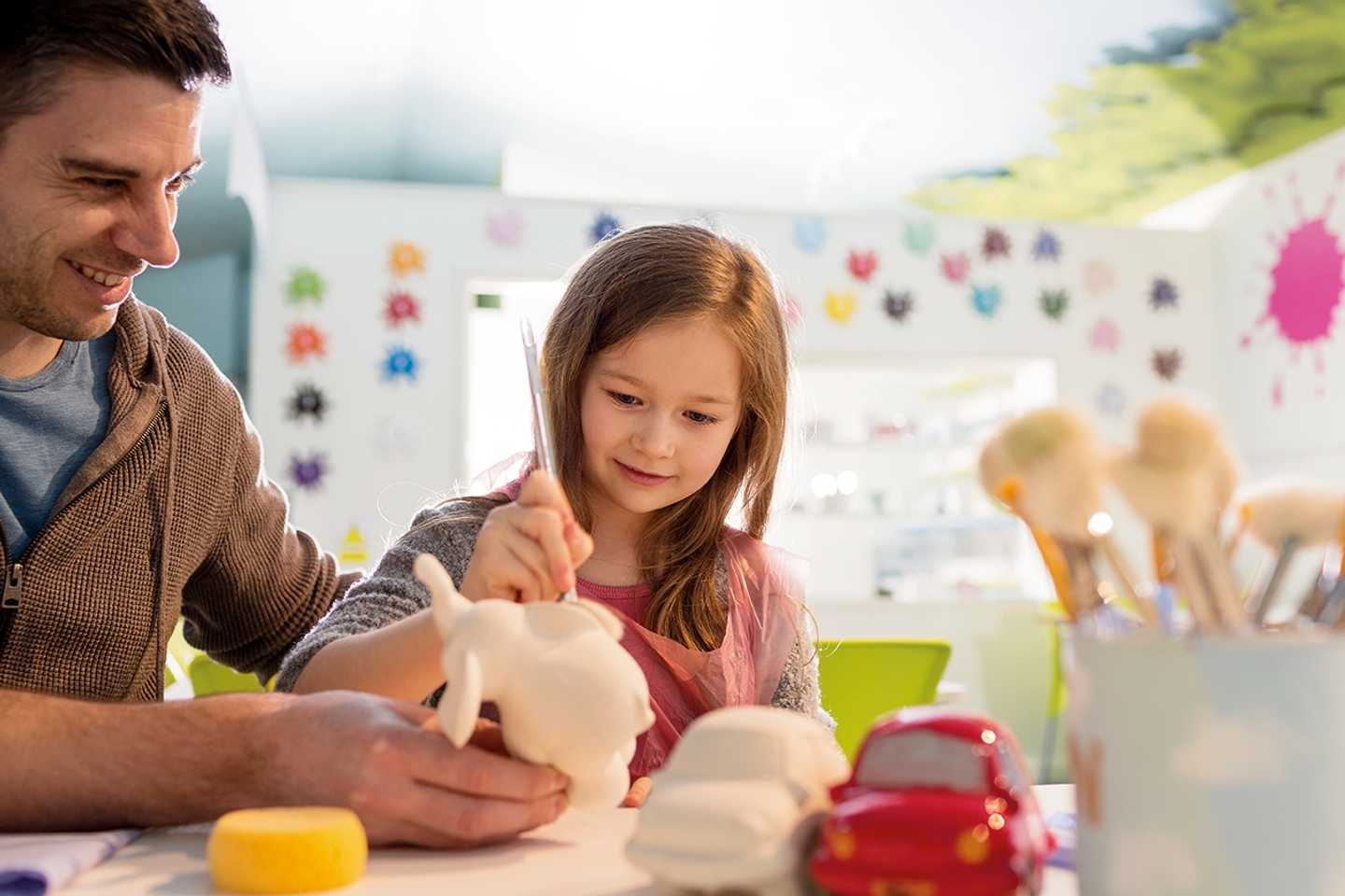 Dad and daughter painting pottery