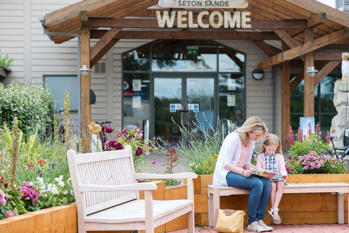 Mother and Daughter sitting on a bench near the entrance to Seton Sands Holiday Village