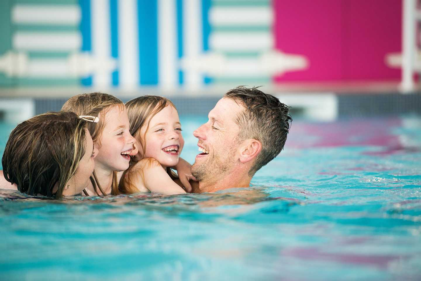 A family smiling as they spend time together in the indoor pool
