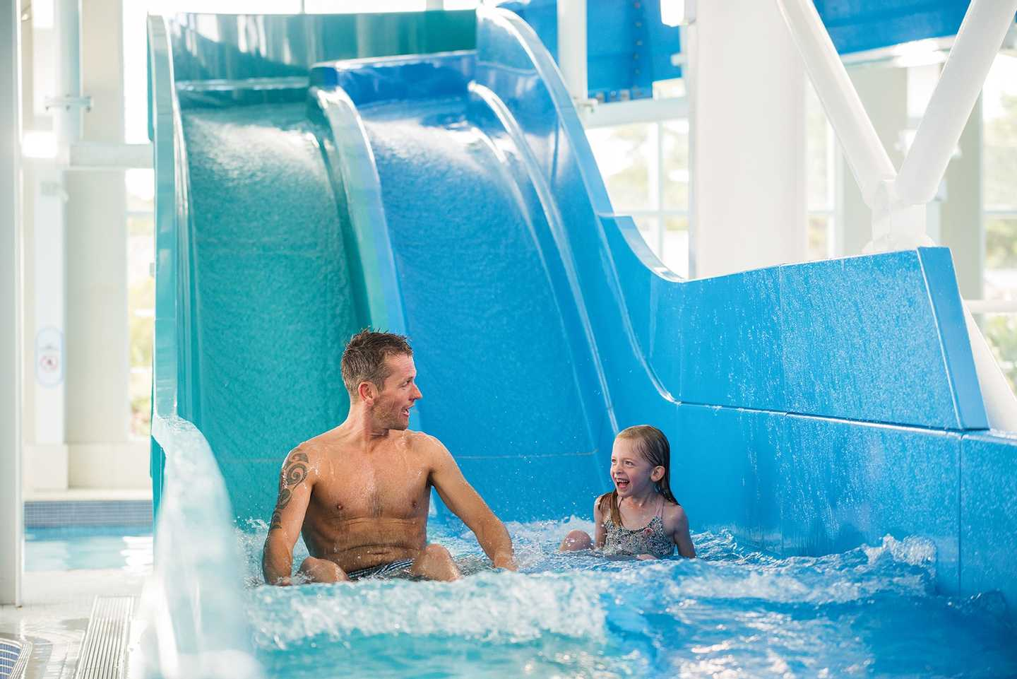 Parent and child going down the racing water slides at Seton Sands, Scotland