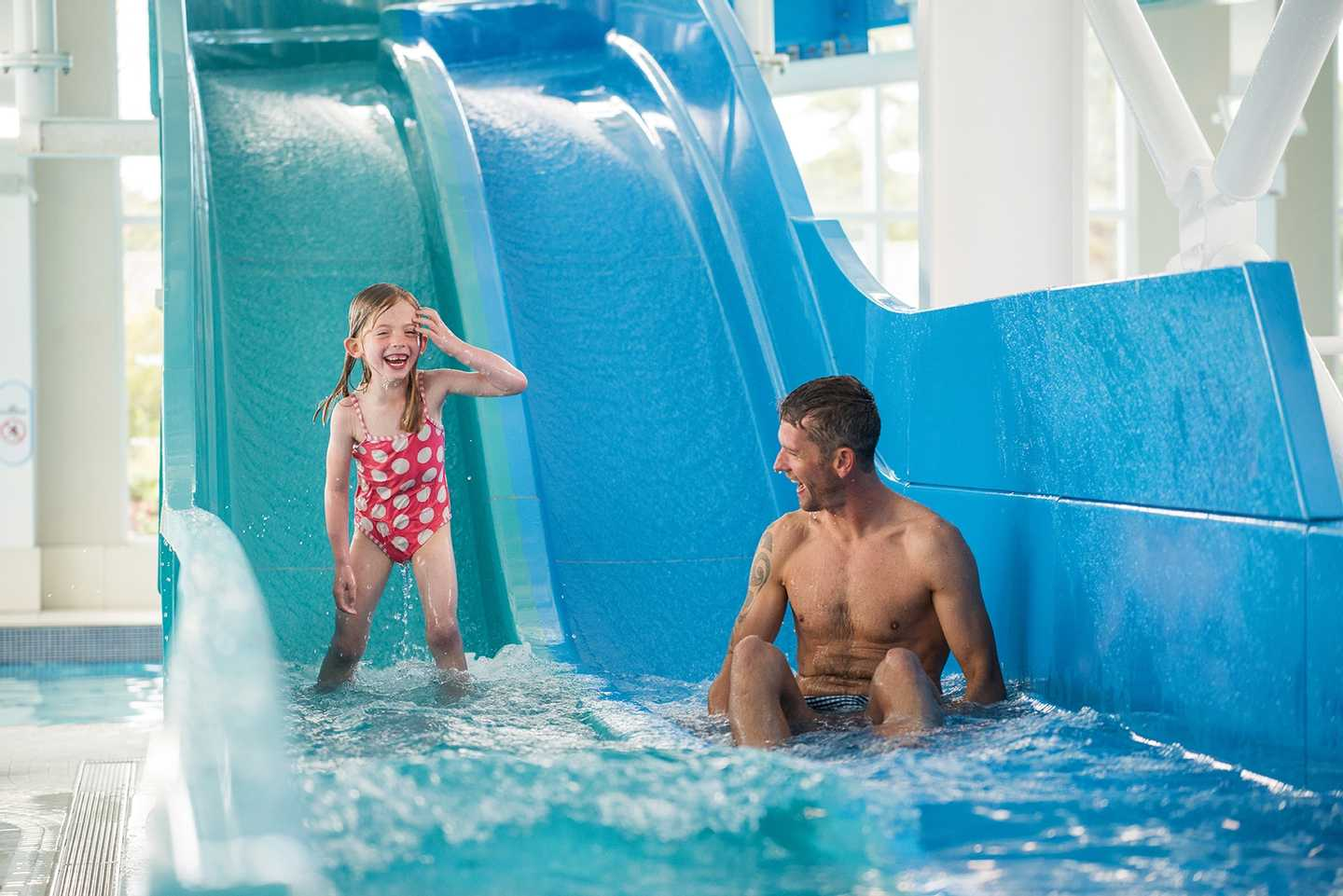 Parent and child going down the slide in the indoor pool at Seton Sands, Scotland