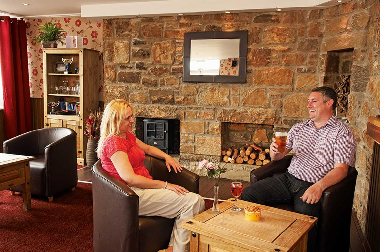 A couple enjoying a drink in our rustic and farmhouse looking Owners' Lounge at Seton Sands Holiday Park