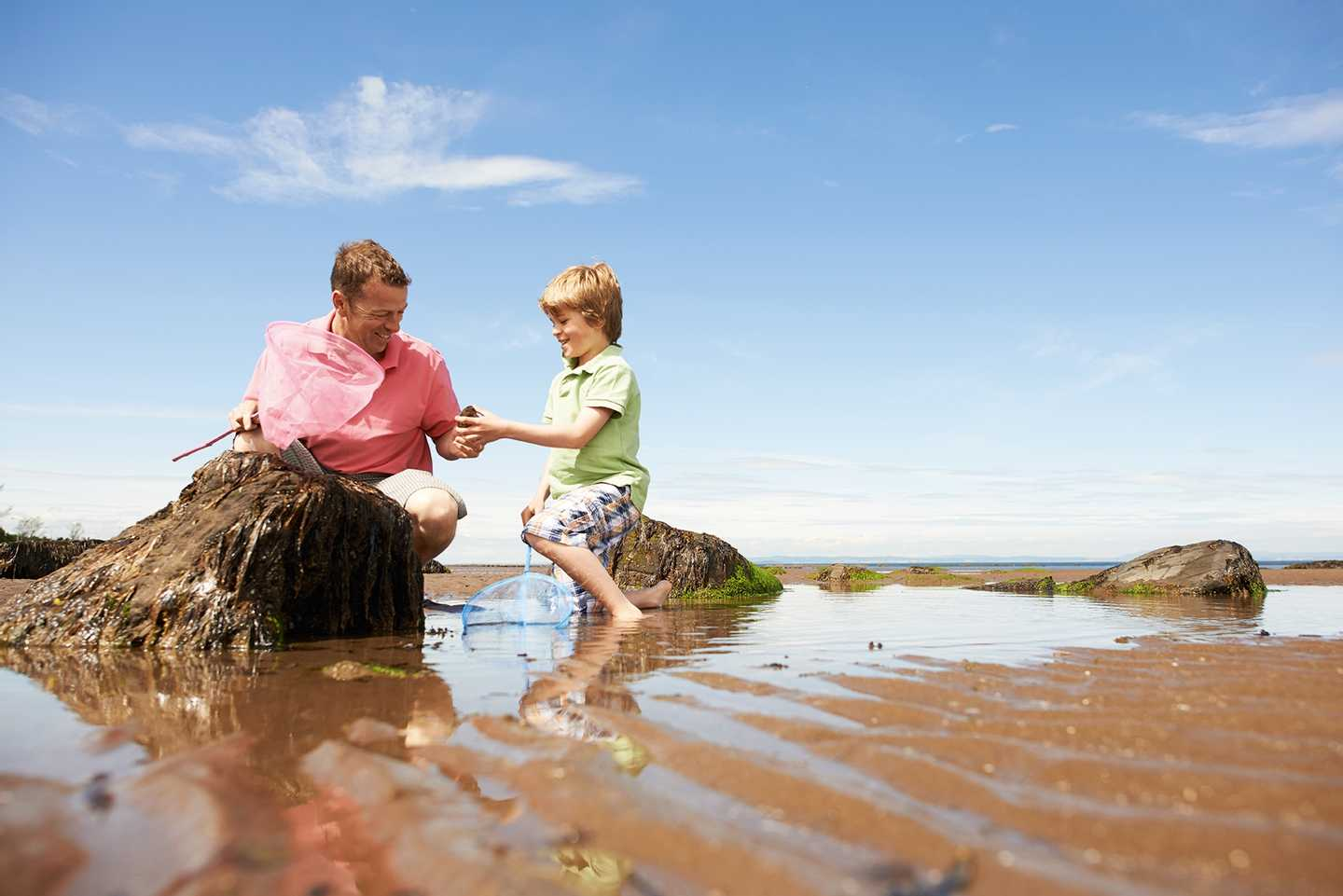 Parent and child rock pooling on the beach at Seton Sands, Scotland