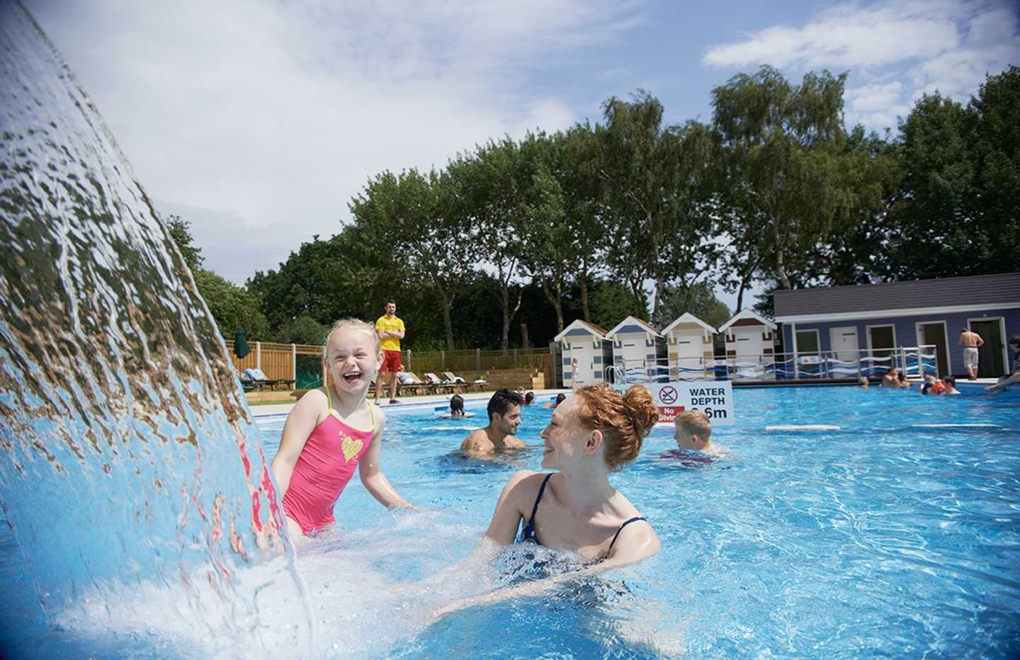 Family having fun in outdoor pool water feature