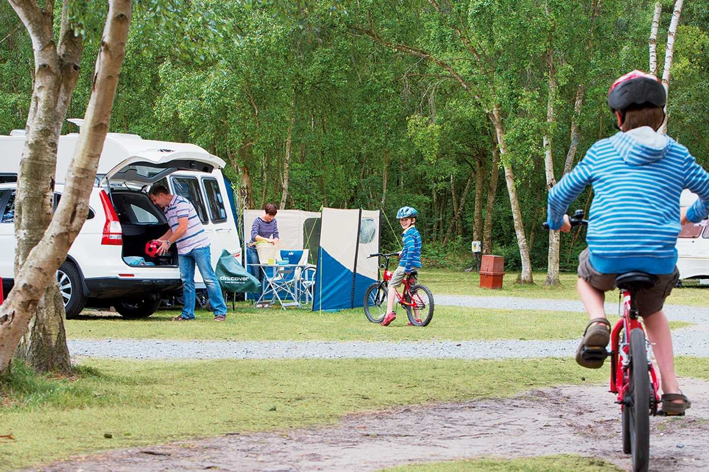 A boy riding a bike through the touring and camping area at Wild Duck