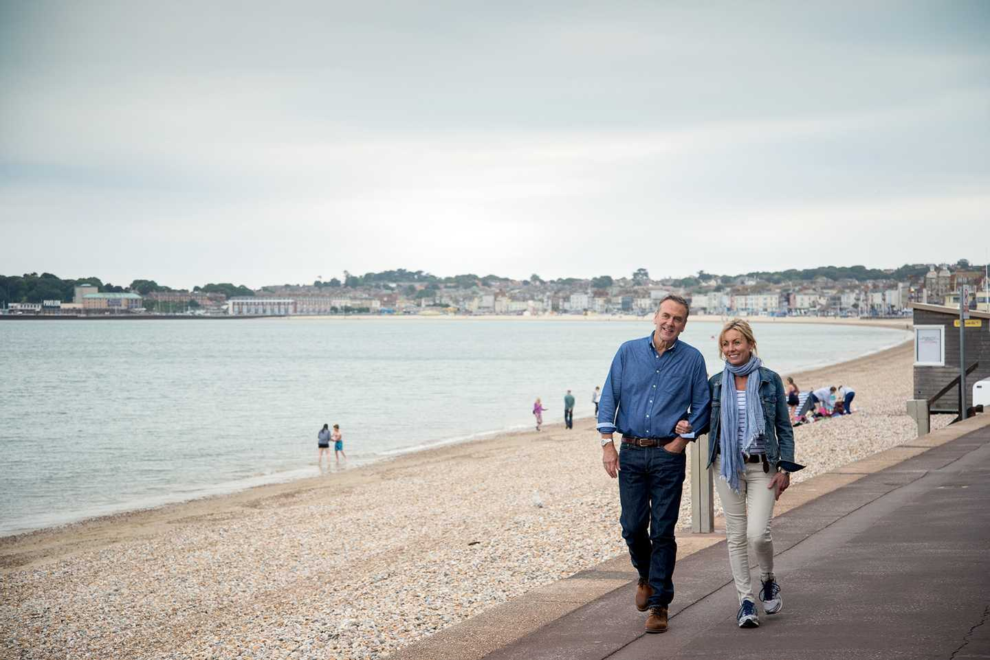 A couple walking along the promenade of a shingle beach, arm in arm with the sea and cloudy skies in the background