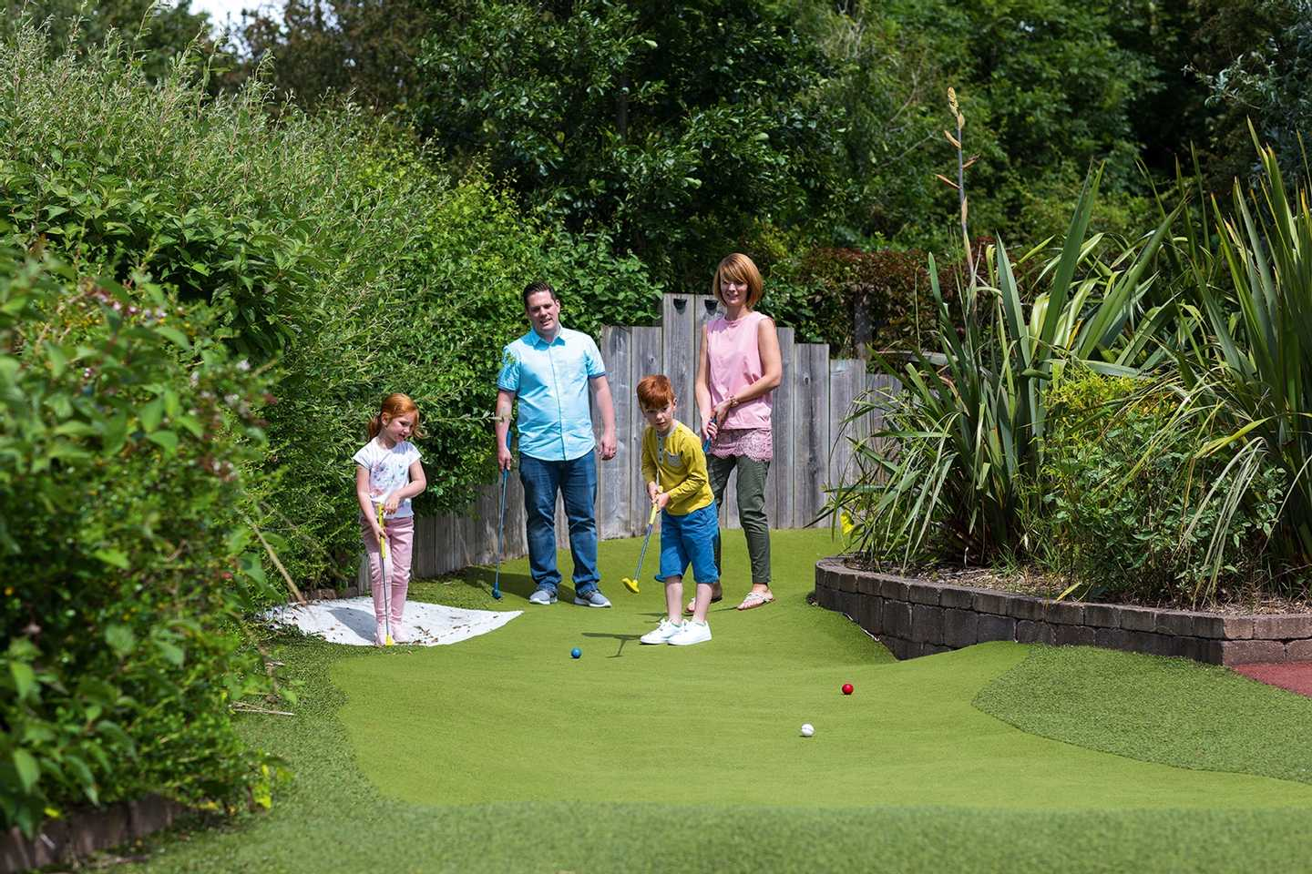Family playing on the adventure golf course at Cala Gran