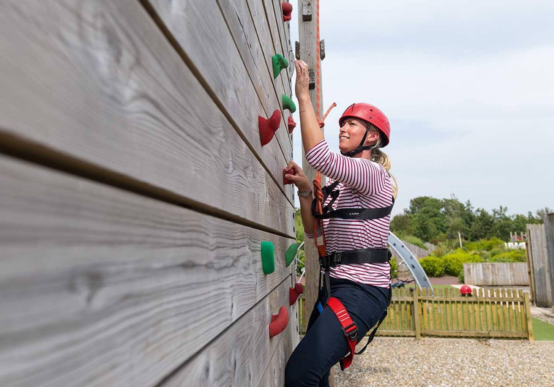 A guest climbing up the climbing wall at Cala Gran