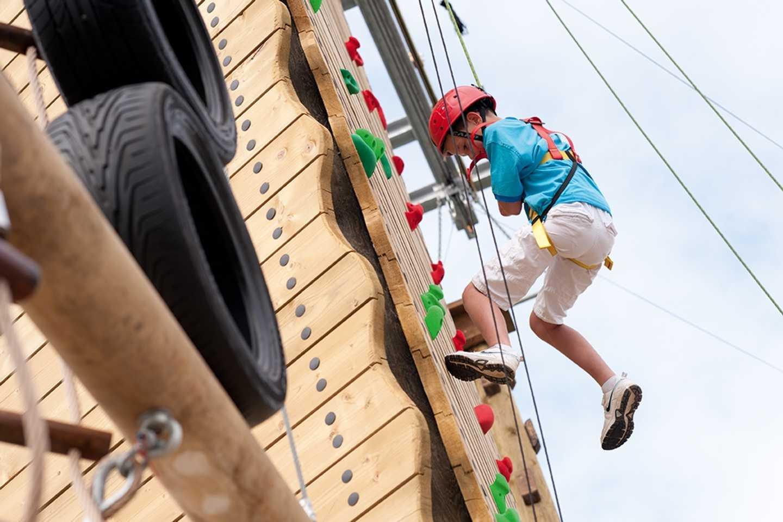 A young boy climbing the climbing wall