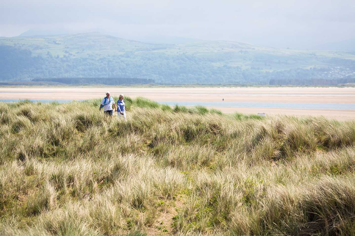 A view of a couple walking across the top of grassy sand dunes near our park, with sand, sea and mountains with mist around them in the background