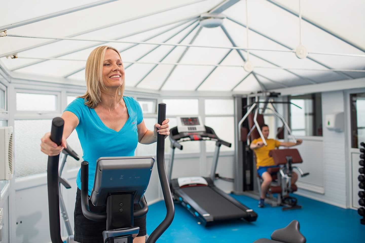 A lady working out on the cross trainer in the owners' gym