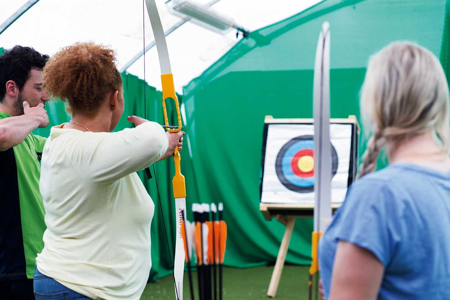 Guest being shown how to shoot the archery bow
