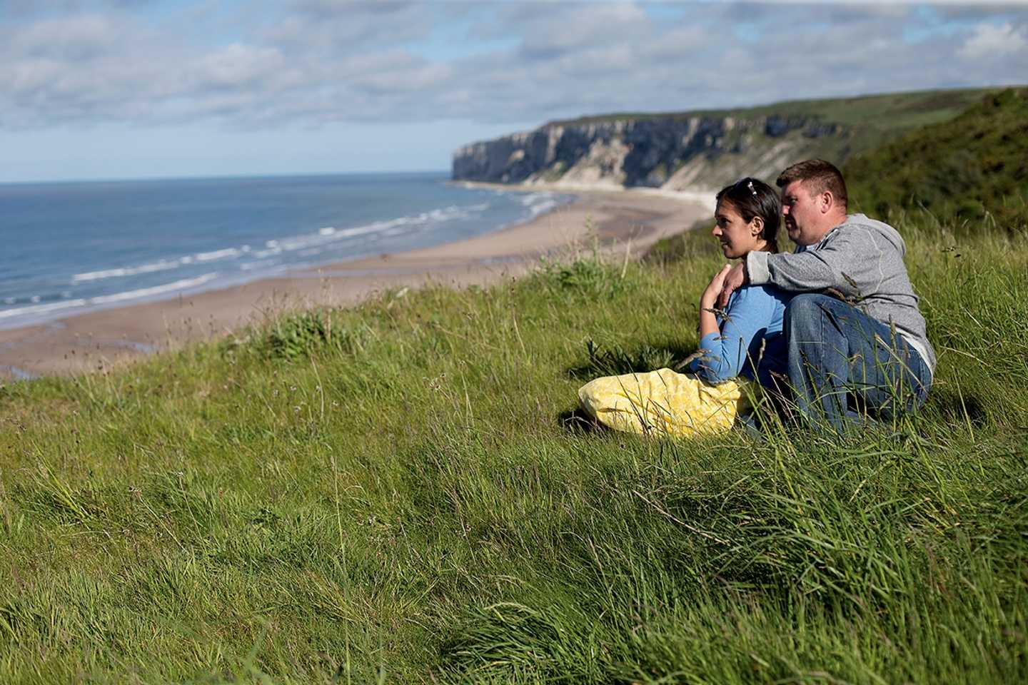 A couple hugging each other as they look at the sea and cliffs near Reighton Sands