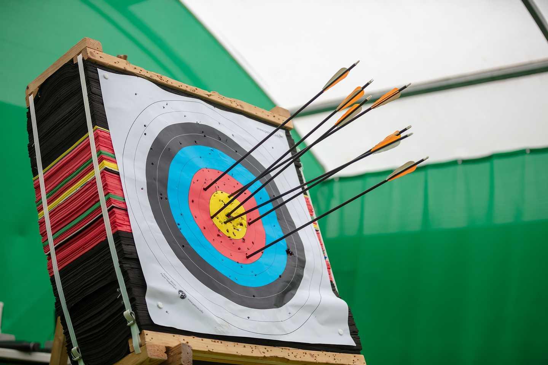 Boy pulling arrows from archery board