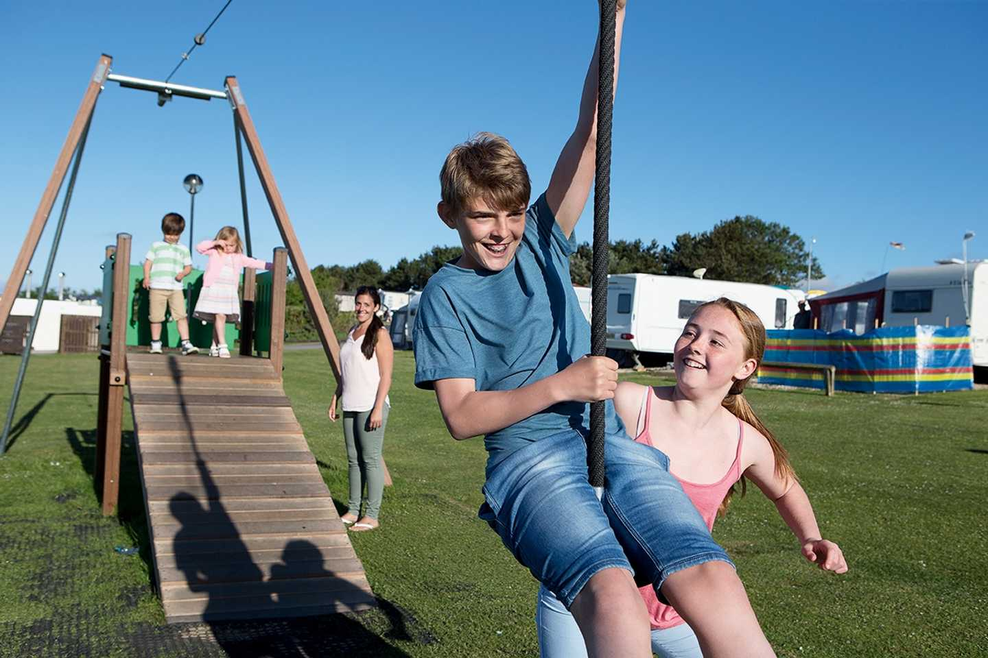 Children playing on the zip wire in the touring play area