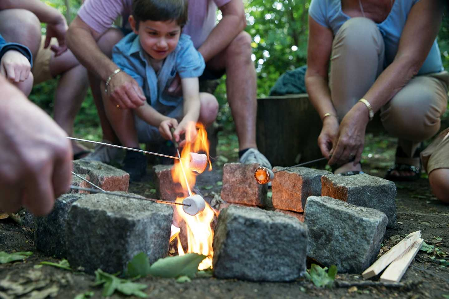 Helping a child toast marshmallows at the Nature Rockz activity