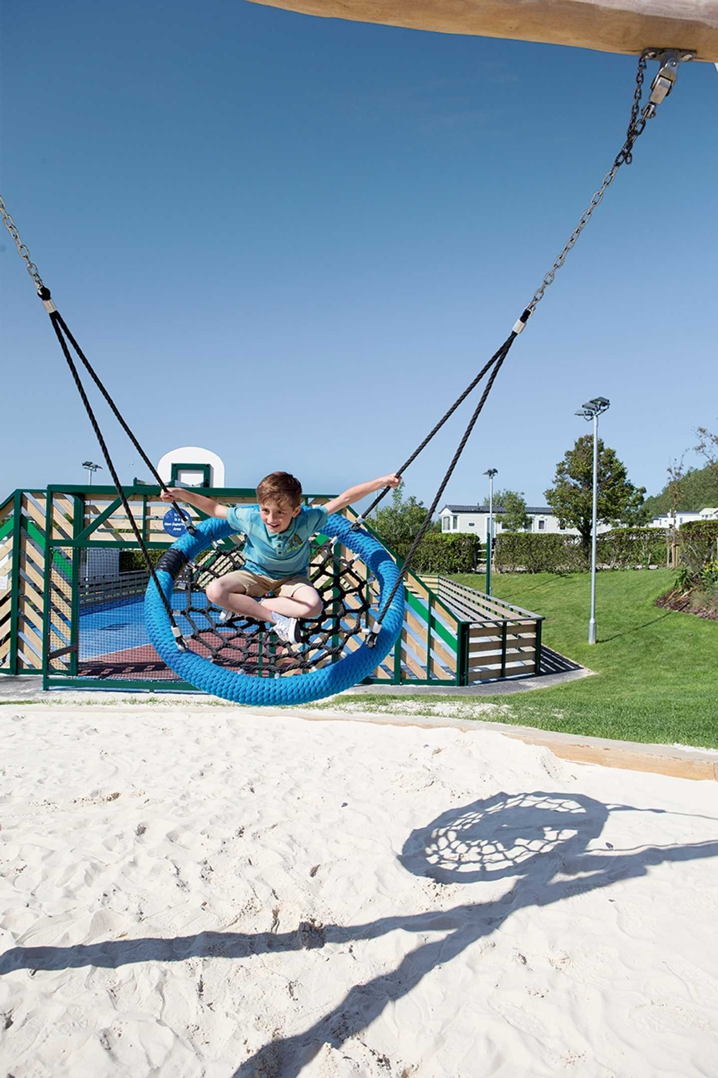 Children swinging in the nest swing in the outdoor play area
