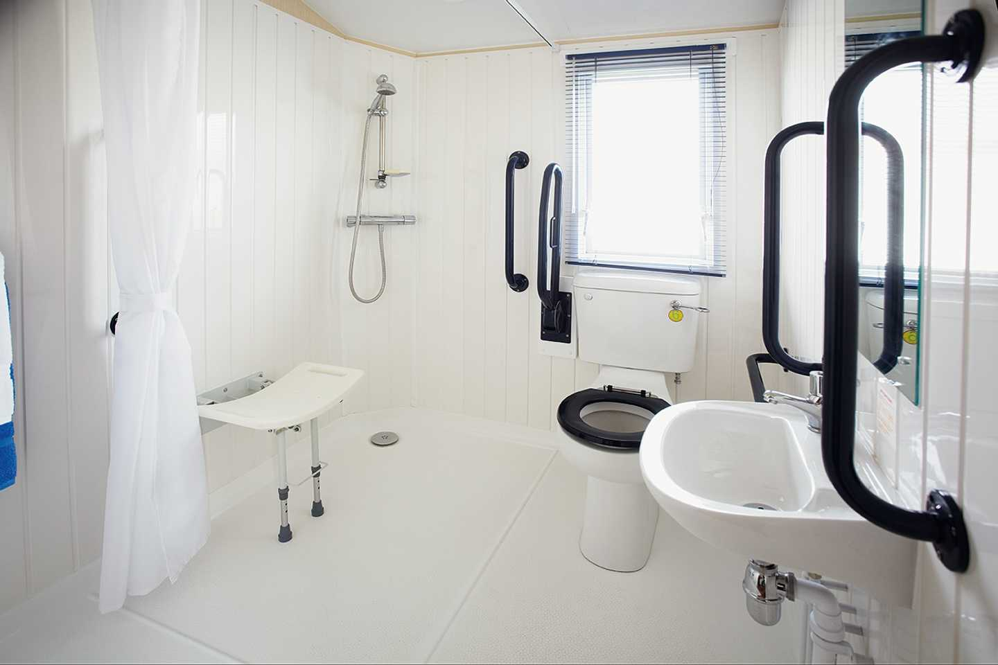 An Adapted caravan bathroom with a sit down shower, sink and toilet