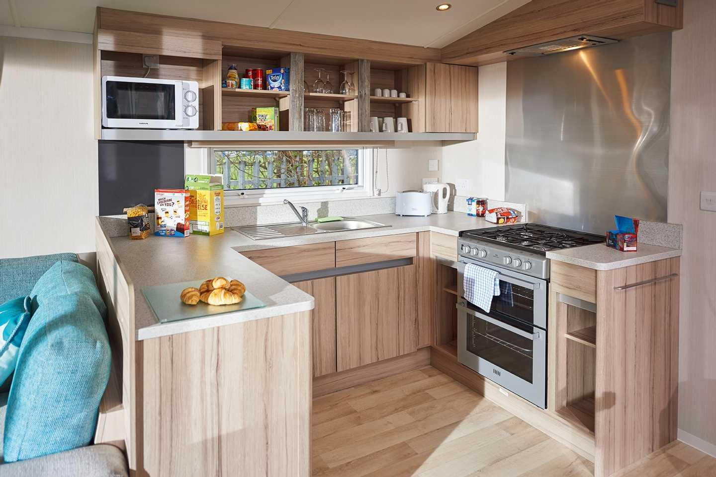 A newer Deluxe caravan kitchen with cooker, microwave, kettle and toaster