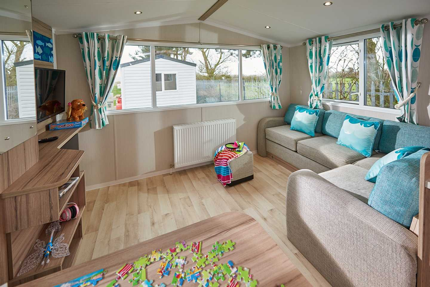 A newer Deluxe caravan lounge with TV, sofa and dining table
