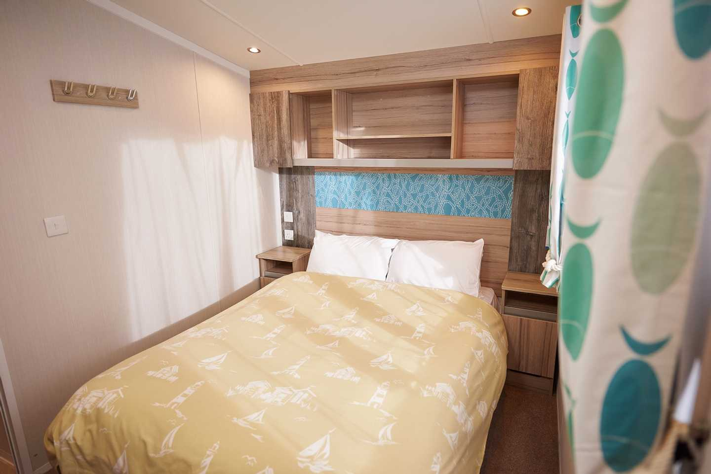 A newer Deluxe caravan master bedroom with double bed and side tables