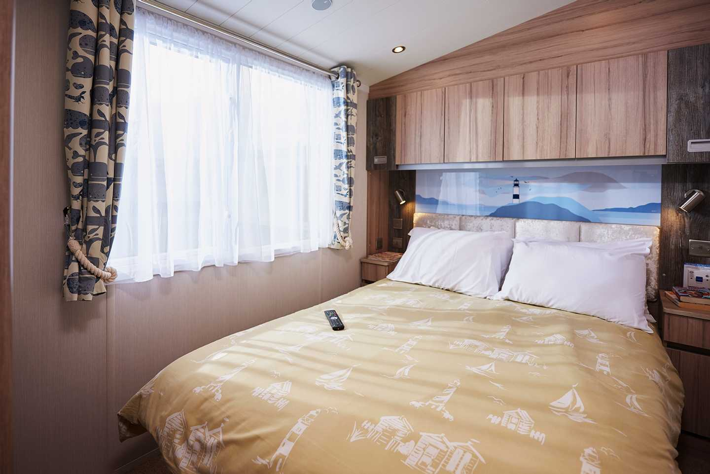 A Platinum caravan master bedroom with double bed, bedside tables and overhead cupboards