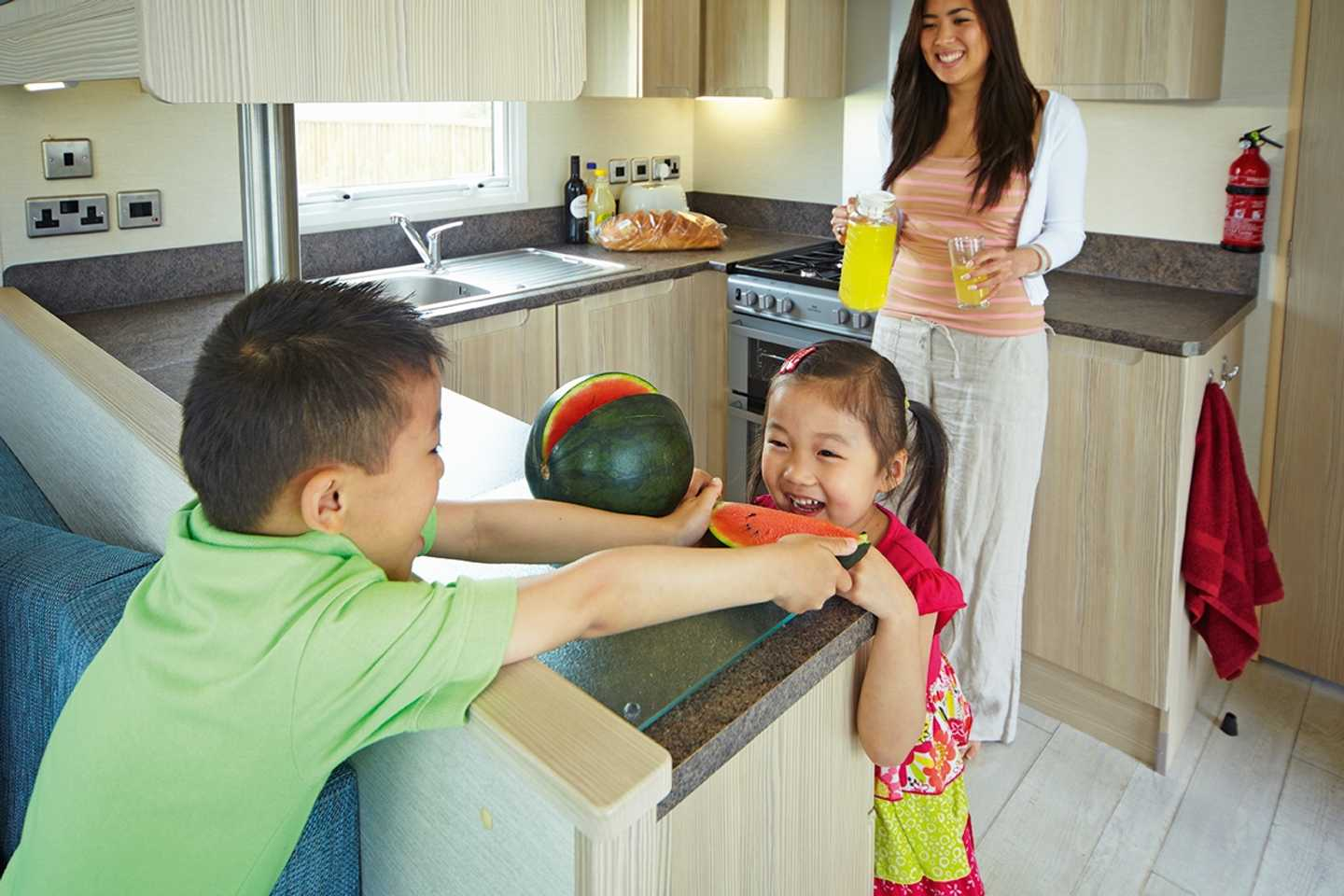 A Prestige caravan kitchen with a family enjoying a water melon and orange juice