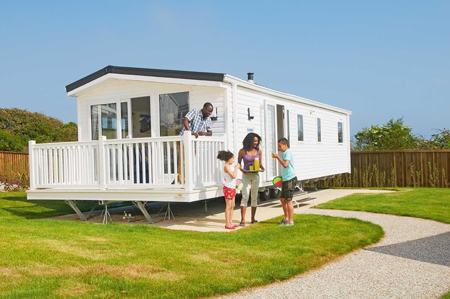 Family outside a Prestige with Decking caravan