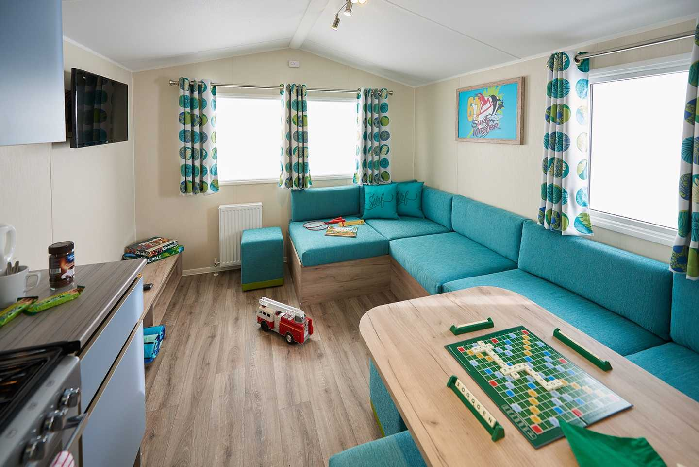 A newer Standard caravan lounge with sofa, TV and dining table