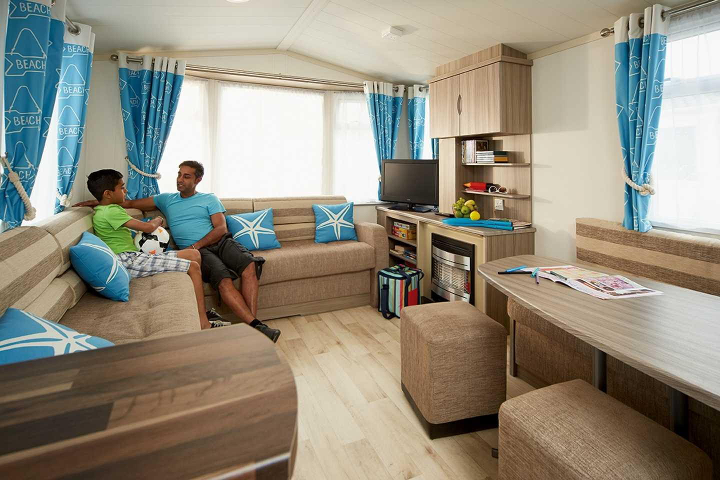 A Standard caravan lounge with a father and son sitting on the sofa talking