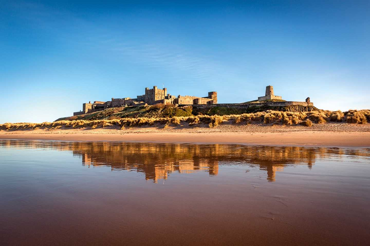 A view of Bamburgh Castle high up on the hill from the beach