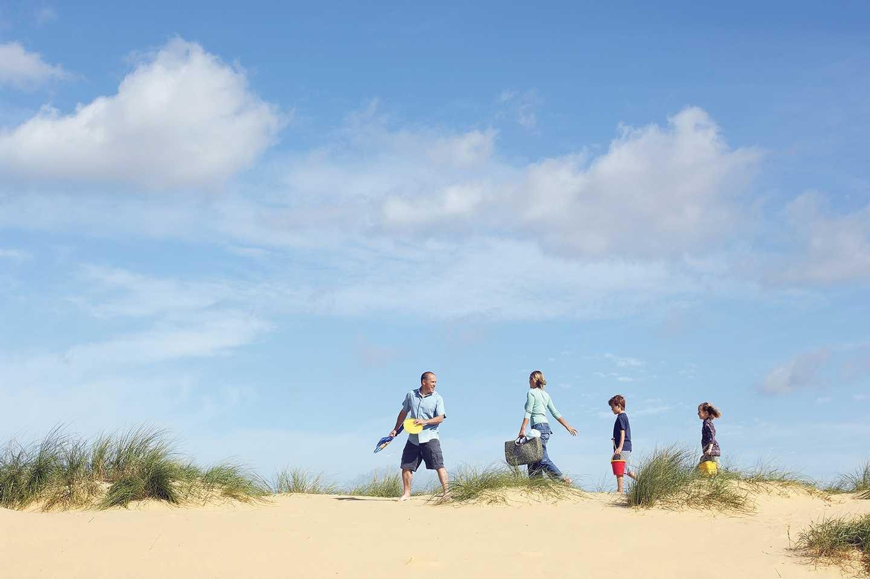 People walking along Holme Dunes