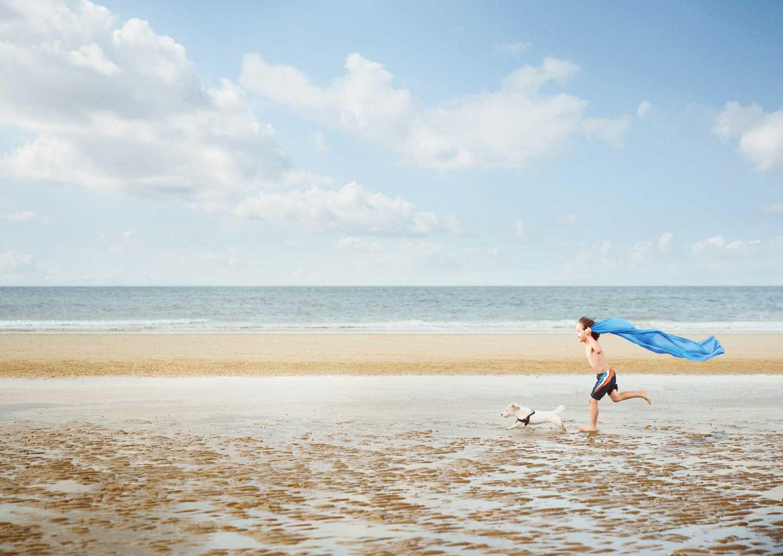 Little boy running across the beach with a blue beach towel like a cape