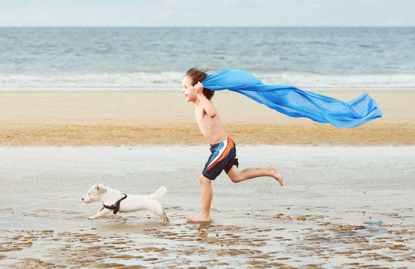 Boy and dog running down the beach at Haven