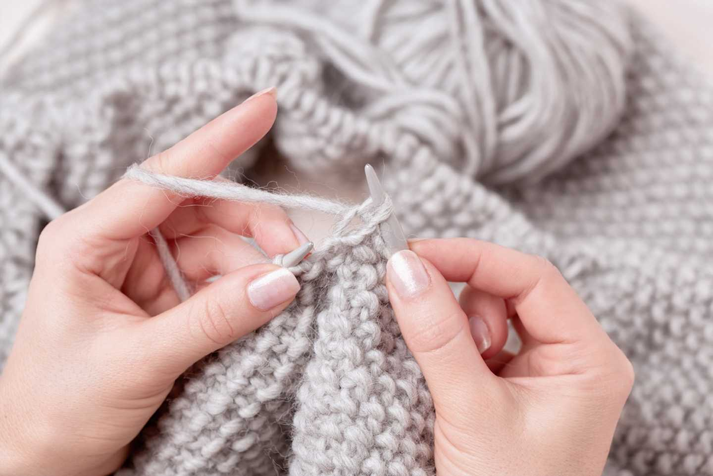 A lady knitting with natural coloured wool