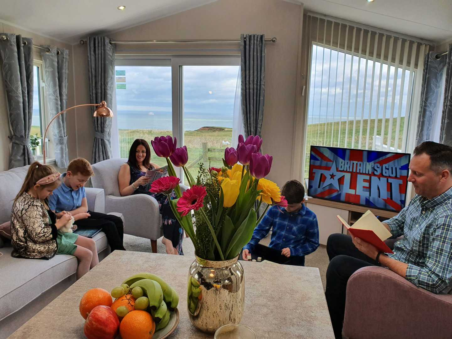 Family sat in lounge of their holiday home watching Britain's Got Talent