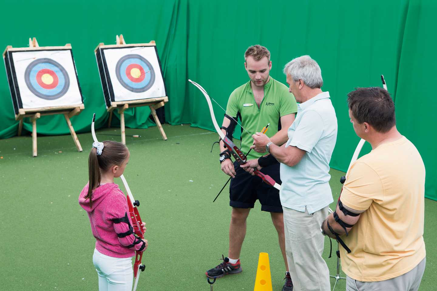 An archery instructor teaching family how to play