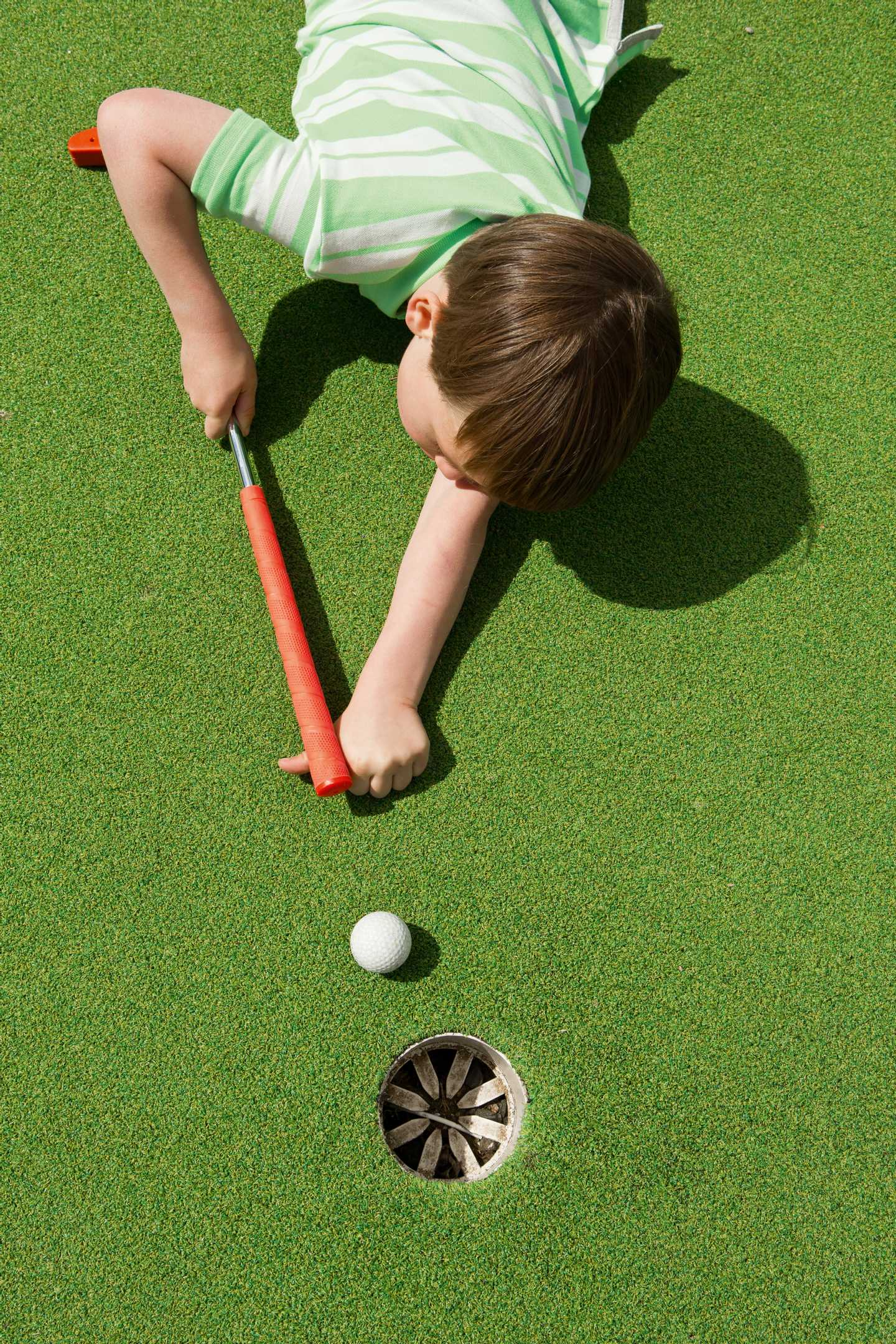 A boy trying to pot a golf ball on the Adventure Golf course