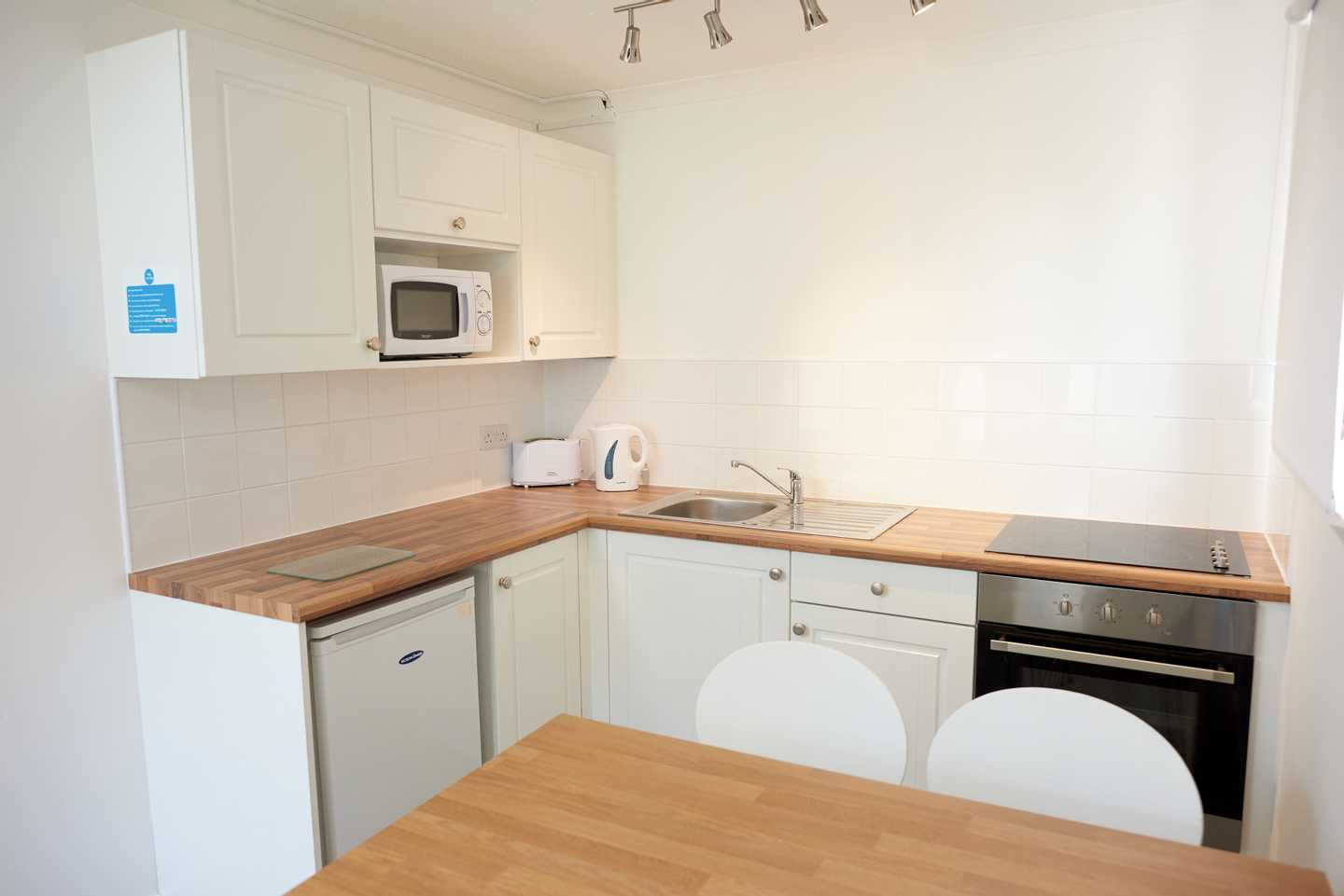 A Comfort apartment kitchen with cooker, sink, kettle, toaster, microwave and storage cupboards