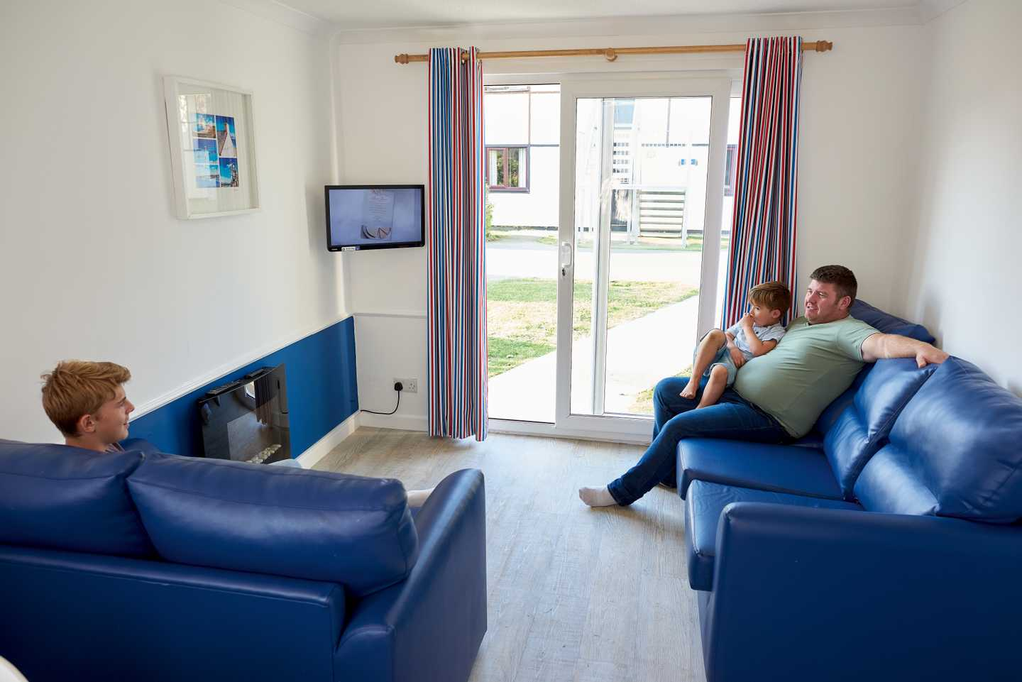 A family watching TV in a Comfort apartment with fireplace, blue sofas and sliding doors