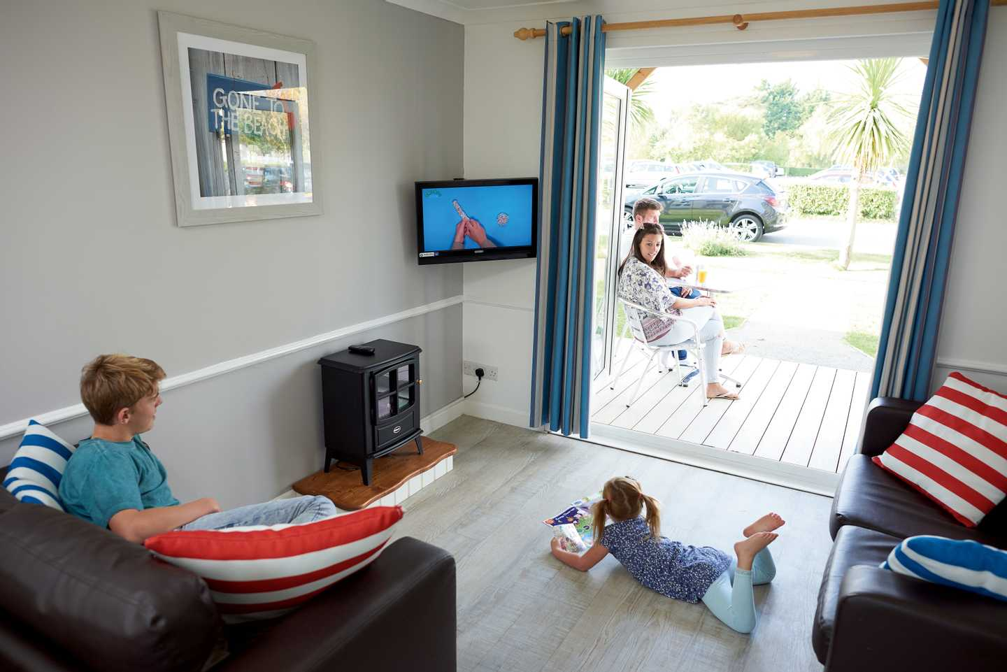 Two children watching TV in a Comfort with Veranda apartment with parents outside on the decking