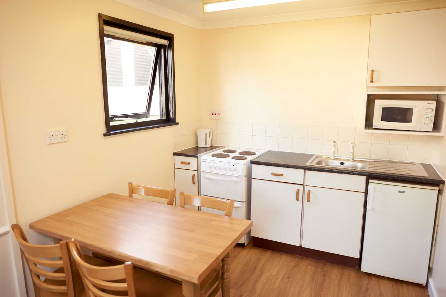 A Standard apartment kitchen with a dining table, chairs, cooker, microwave and kettle