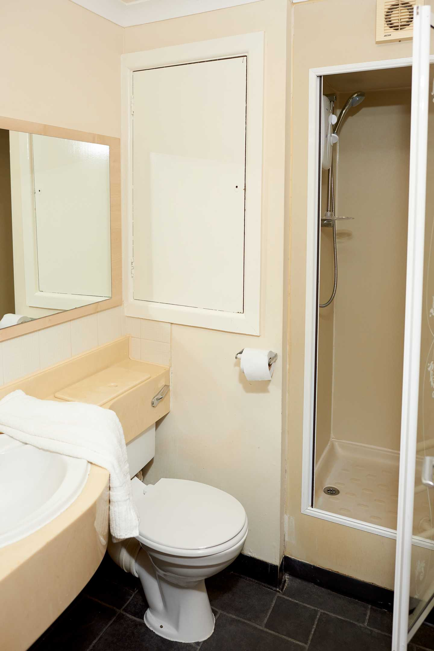 A Standard apartment bathroom with a toilet, shower, sink and mirror