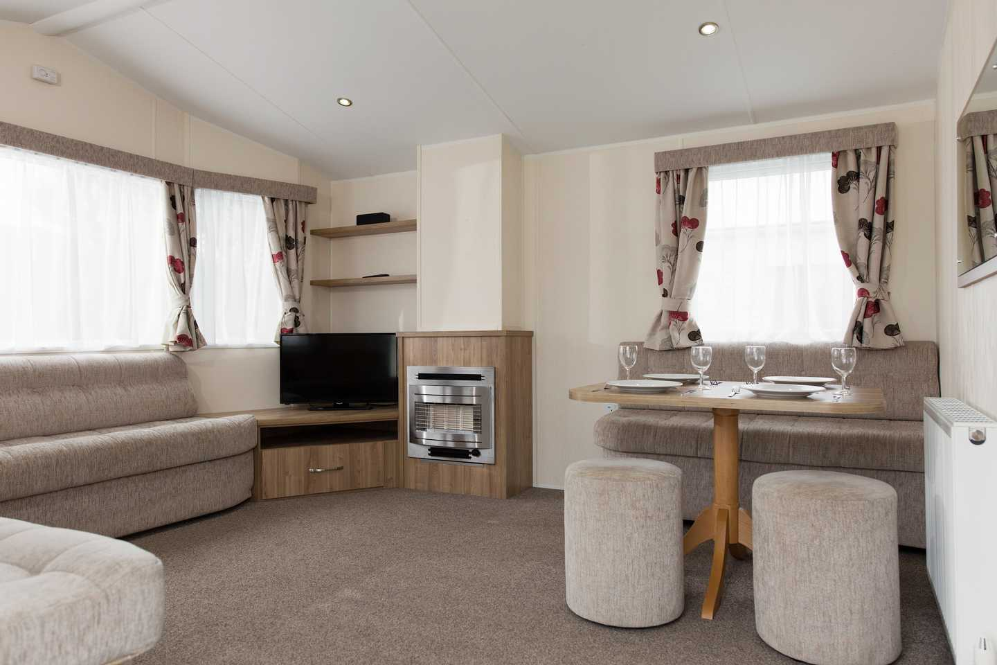 An Adapted caravan with dining area, TV, fireplace and sofa