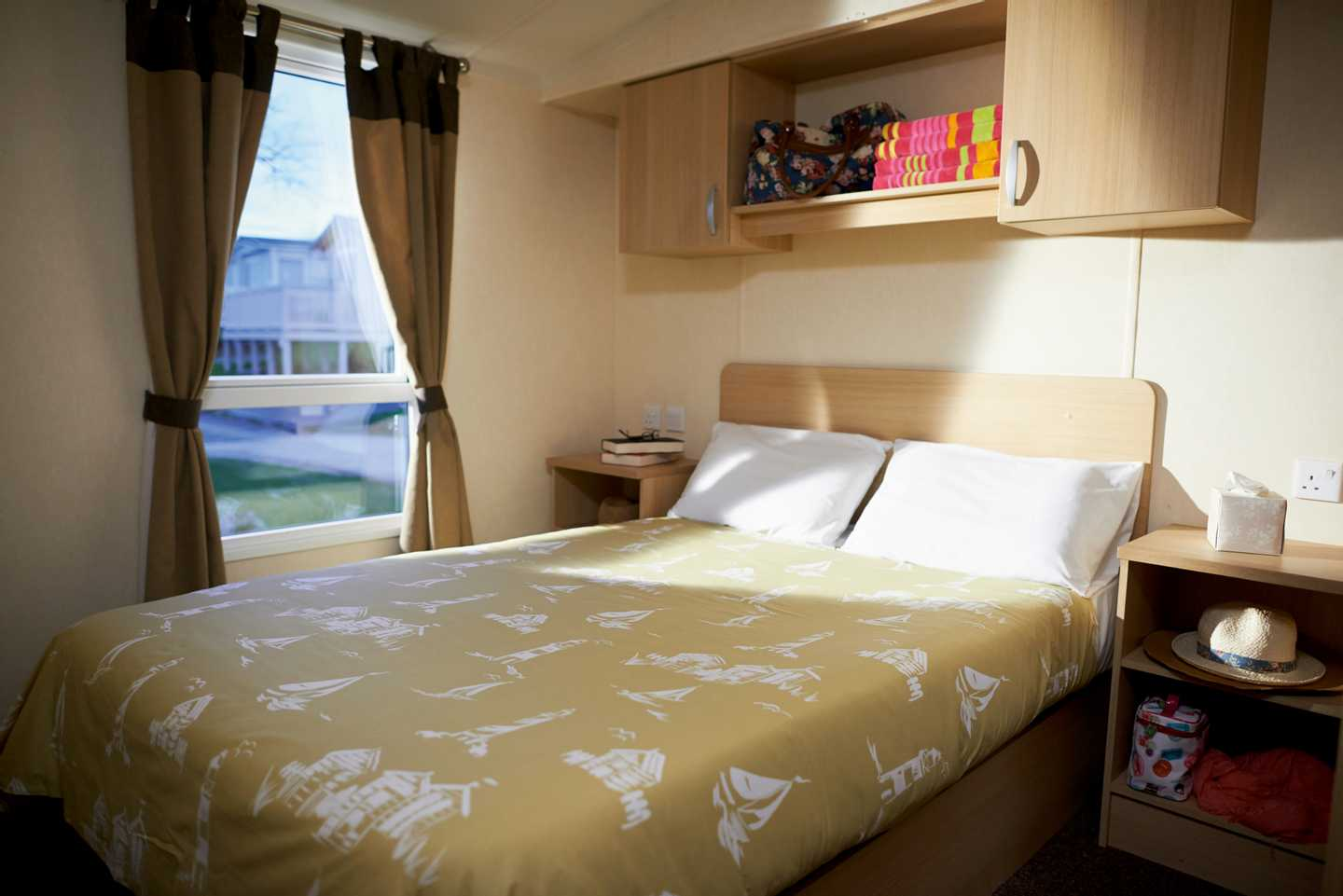 A Deluxe caravan master bedroom with a double bed, two bedside cabinets and overhead storage