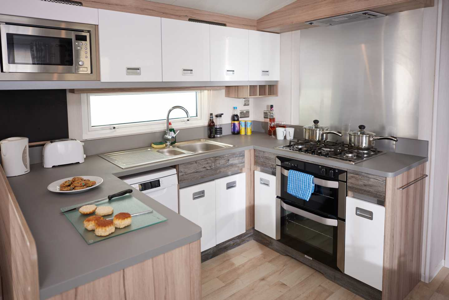 A Platinum with Decking caravan kitchen with oven, microwave and cookies on the kitchen top